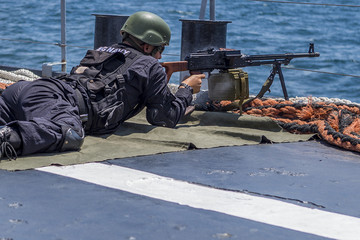 Soldier Shooting with a Machine Gun on a Black Sea Battle / Bulgaria / 07.19.2018 /sailor in black camouflage and shoes is preparing to shoot from the deck of a warship.
