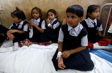 Students wait to be examined by doctors at a hospital after one student died from a suspected medicine poisoning, according to local media, in Mumbai