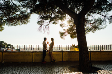 Young couple hugging each other in the street of Lisbon, Portugal. Romantic relationships concept