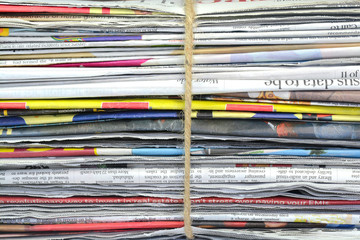 Stack of newspaper bundle tied with jute rope.