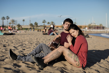 Spain, Barcelona, couple with a guitar sitting on the beach