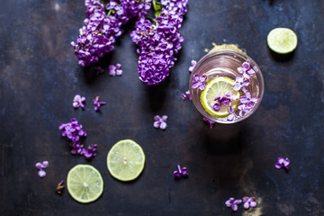 Glass of homemade lilac lemonade with slices of limes