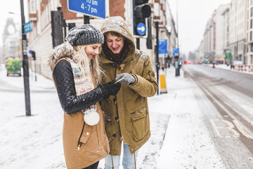 UK, London, young couple standing at roadside looking at cell phone on a snowy day