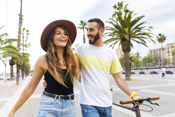 Spain, Barcelona, happy couple walking on seaside promenade