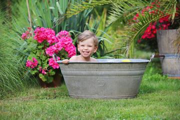 Ein kleiner Junge sitzt in einer verzinkten Badewanne
