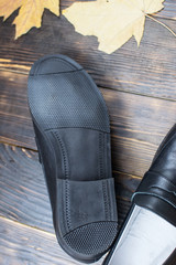 black school shoes for a boy without laces on a wooden surface
