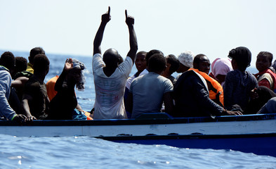 Migrants on a wooden boat react as they wait to be rescued by SOS Mediterranee organisation and Doctors Without Borders during a search and rescue (SAR) operation with the MV Aquarius rescue ship in the Mediterranean Sea