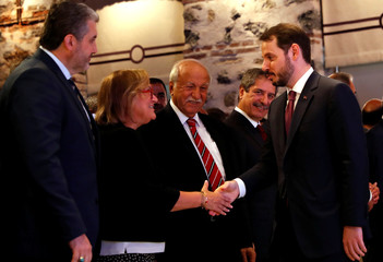 Turkish Treasury and Finance Minister Albayrak shakes hands with Guler Sabanci, Sabanci Group Chairman of the Board, before a presentation to announce his economic policy in Istanbul