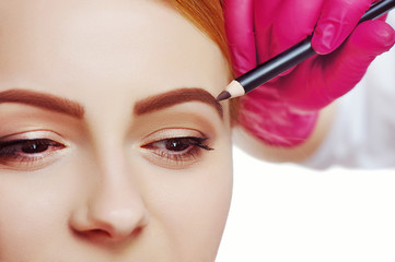 Closeup picture of eyebrows shape correction with a cosmetic pencil