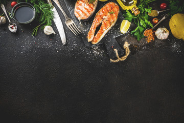 Grilled salmon fish steaks with ingredients lemon, herbs, olive oil, slate cutting board, dark rusty background copy space