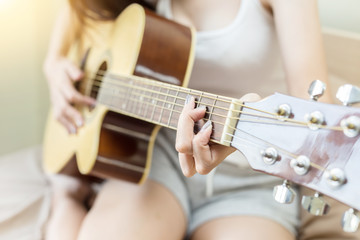 woman playing guitar in bedroom for singing music and relax feeling so happiness and enjoy with it