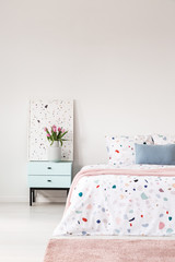 Cropped photo of a bed with lastrico sheets, pink rug and bedside table with a vase of flowers and graphic. Empty wall, place for your painting/graphic/poster