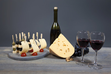 Harmonious composition bottle of red wine with two glasses, cheese, a bunch of grapes. Isolated on gray background