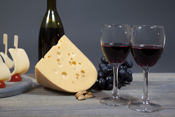Two glasses with red wine on a wooden table. Cheese and bunch of grapes harmoniously complement the composition