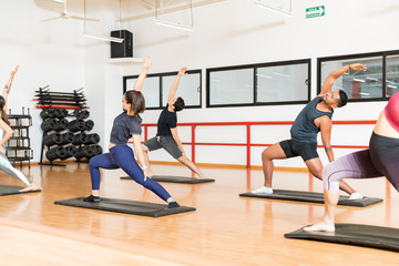 Determined Clients Performing Reverse Warrior Pose In Gym