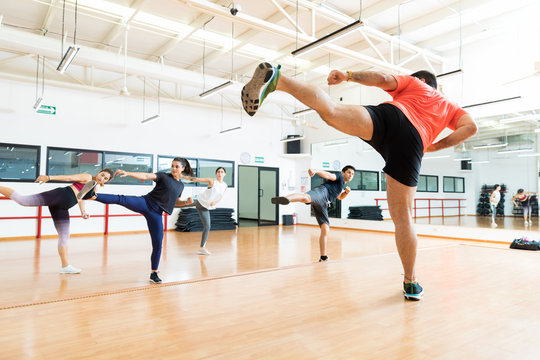 Instructor And Clients Kickboxing In Dance Class At Gym