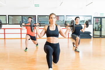 Dedicated Woman Lifting Weights With Friends In Health Club
