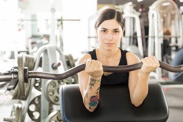 Confident Female Athlete Lifting Barbell Curl On Exercise Machine