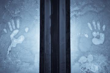 Human palms on frosty window
