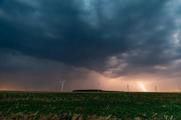 Un soir d'été, l'orage gronde et des arcs d'éclairs fendent le ciel sur les éoliennes et les champs de campagne en Moselle