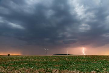 Un soir d'été, l'orage gronde et un éclair fend le ciel et les nuages gorgés de pluie passent sur les éoliennes et les champs de campagne en Moselle