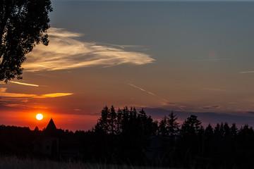 Le soleil se couche  sur les toits et sapin d'un village en Alsace