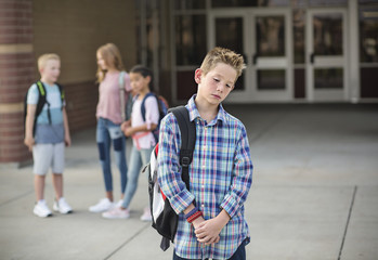 Sad boy feeling left out, teased and bullied by his classmates. Unhappy boy having problems fitting in with others at school Wall mural