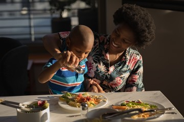 Mother and son sprinkling salt on food
