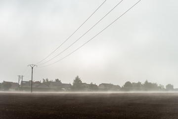 Un matin d'été au lendemain d'un orage, la rosée monte comme une brume au pied d'un village de Moselle