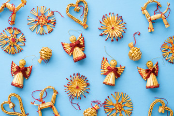 Flat lay assortment of scandinavian christmas straw decorations on a blue background
