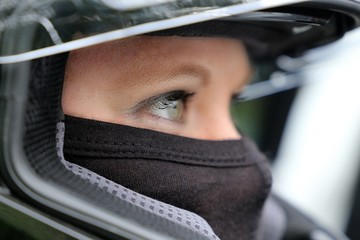 Foto op Canvas Motorsport Rennfahrerin mit Helm und Sturmhaube