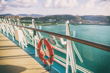 Cruise ship Caribbean vacation travel tropical holidays. View of landscape at sunset from boat balcony deck with railing and red lifebuoy. Getaway on sea.