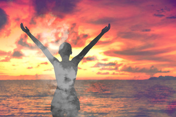Freedom woman double exposure clouds sky sunset meditating with open arms in wellness and zen. Meditation concept.