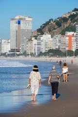 Women walking on the beach of Copacabana, Rio de Janeiro