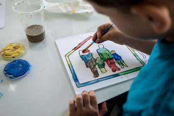 Young boy coloring in an outline sketch with paint