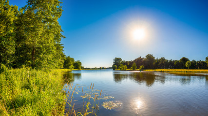 Summer landscape with trees, meadows, river and bright sun Fototapete