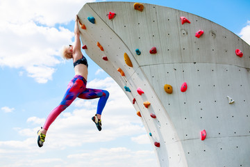 Photo of sporty girl in leggings hanging on wall for rock climbing against blue sky