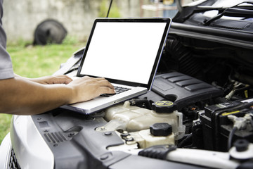 Professional mechanic checking car engine search for data with laptop and connect data system on car
