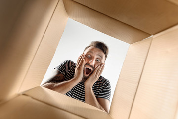 The surprised man unpacking, opening carton box and looking inside. The package, delivery, surprise, gift lifestyle concept. Human emotions and facial expressions concepts