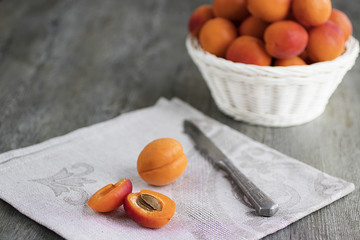 Ripe bright apricots in white basket, knife and gray napkin on wooden gray table.