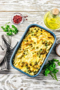 Healthy yellow string bean casserole with green peas and parmesan cheese. Top view, space for text.