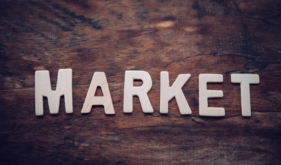 "Place the word ""MARKET"" white on the wooden floor."