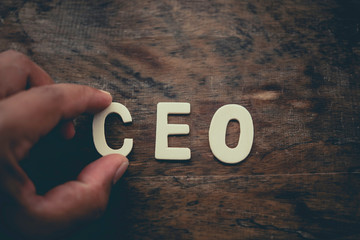"""Place the word """"CEO"""" white on the wooden floor."""