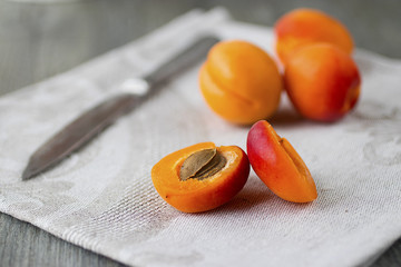 Ripe bright apricots, knife and gray napkin on wooden gray table.
