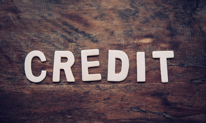 "The word ""CREDIT"" is arranged from a wooden letter placed on a wooden floor."