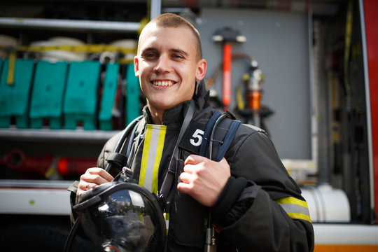 Photo of happy firefighter standing near fire truck with fire hose
