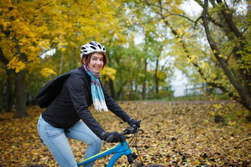 Photo of happy girl in helmet riding bicycle in autumn