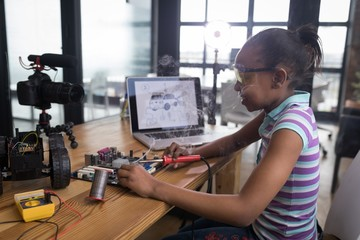 Teenage blogger soldering a circuit board