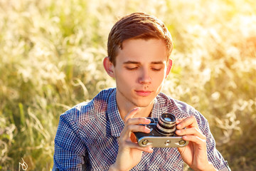 a young man with a camera taking pictures of the natural background sun rays tinted