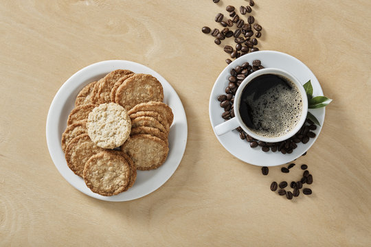 Cup of black coffee whit cookies on white plate and wooden background. Top view.